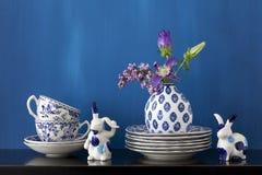 与蓝色和白色盘和花的静物画在小的VA 免版税库存图片