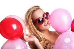 戴拿着红色桃红色气球, VA的眼镜的年轻美丽的妇女 免版税库存照片