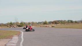 Va-Kart la pista Dos karts que se mueven en la cámara y el paso cerca almacen de video