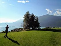 VA man playing golf along the ocean in howe sound, British Columbia, Canada. It is a beautiful sunny day. royalty free stock photo