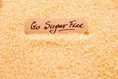 Va Sugar Free - manuscrito en la etiqueta que se sienta en granul del azúcar crudo Foto de archivo