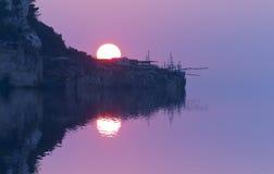 Vaag beeld van bezinningen over overzees bij zonsondergang met zachte nadruk van zon en trabocco Stock Foto