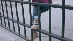 Vaag beeld van de voeten die van het meisje op omheining beklimmen stock video