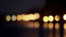 Vaag die licht van de nachtlichten in rivierwater worden weerspiegeld stock video