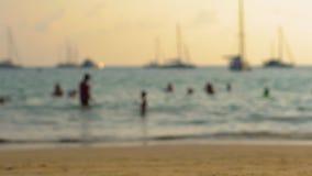 Vaag schot van een bezig strand in keerkringen met silhouetten van mensen die voorbijgaan stock footage