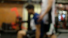 Vaag van mensenoefening met trainer het steunen binnen de gymnastiek stock video