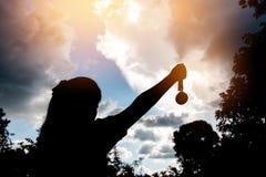 Vaag van silhouet overhandigt opgeheven en holding gouden medailles met Royalty-vrije Stock Foto