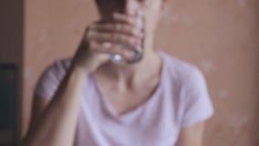 Vaag vrouwen drinkwater van een transparant duidelijk glas stock footage