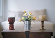 Vaas met gele en groene bloemen, met een kaart die gelukkige dag zegt stock foto's