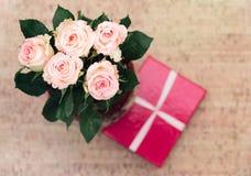 Vaas met rozen en gift met lint stock afbeeldingen