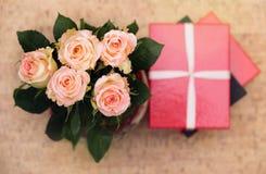 Vaas met rozen en gift met lint stock afbeelding