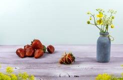 Vaas met wildflowers Één of andere aardbei is op de lijst Jonge volwassenen royalty-vrije stock foto