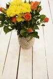 Vaas van bloemen op een witte rustieke lijst Hoogste mening Rustieke vaas met oranje rozen en gele chrysanten Witte achtergrond,  Stock Foto's