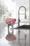Vaas van pioenen op gootsteen van moderne keuken Stock Afbeeldingen