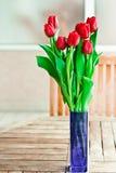 Vaas van rode bloemen op tuinlijst Royalty-vrije Stock Afbeelding