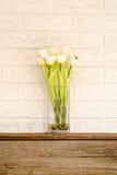 Vaas van witte bloemen op een houten haard Stock Afbeelding