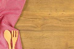 Vaatwerk en geruit rood doekservet op houten achtergrond Royalty-vrije Stock Afbeelding