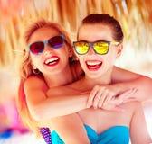 两个美丽的女孩获得在海滩的乐趣在夏天vaca期间 免版税库存照片