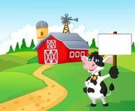 Vaca de la historieta que lleva a cabo la muestra en blanco con el fondo de la granja Imagen de archivo libre de regalías