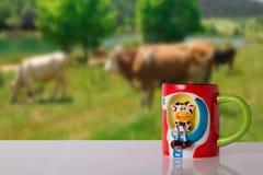 Vaca engraçada como parte de um copo do leite em uma tabela brilhante na frente do bl fotografia de stock royalty free