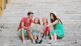 Vacaciones de familia en Europa Padres y niños con el mapa turístico que busca las atracciones metrajes