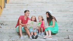 Vacaciones de familia en Europa Padres y niños con el mapa turístico que busca las atracciones almacen de video