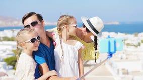 Vacaciones de familia en Europa Padres y niños que toman la ciudad de Mykonos del fondo de la foto del selfie en Grecia almacen de metraje de vídeo