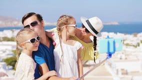 Vacaciones de familia en Europa Padres y niños que toman la ciudad de Mykonos del fondo de la foto del selfie en Grecia metrajes