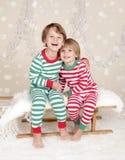 Vacaciones de invierno: Niños felices de risa en el trineo i de los pijamas de la Navidad Imagenes de archivo