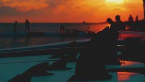 Vacaciones de la playa del verano en la puesta del sol, niños, muchachos que lanzan piedras en el agua en la puesta del sol metrajes