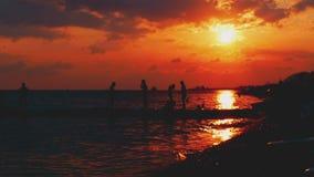 Vacaciones de la playa del verano en la puesta del sol, niños que corren alrededor del puente del baile, jugando a la puesta al d metrajes