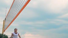 Vacaciones de verano, deporte y concepto de la gente - mujer joven con la bola que juega a voleibol en la playa almacen de metraje de vídeo