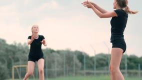 Vacaciones de verano, deporte y concepto de la gente - mujer joven con la bola que juega a voleibol en la playa metrajes