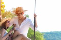 Vacaciones de verano El asiático romántico de la forma de vida junta al amante que juega un ukelele en la hamaca relájese y luna  foto de archivo libre de regalías