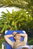 Vacaciones de verano El tomar el sol del hombre joven En el fondo una palmera Concepto de las vacaciones El freelancer del hombre Fotos de archivo
