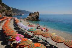 Vacaciones de verano en el italiano Riviera con el paraguas verde anaranjado brillante fotografía de archivo