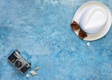 Vacaciones de verano, fondo azul bajo la forma de mar, sombrero, cáscaras fotografía de archivo