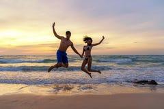 Vacaciones de verano Junte el salto llevando a cabo las manos en tropical en el tiempo de la puesta del sol de la playa en viajes fotos de archivo libres de regalías