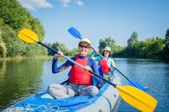 Vacaciones de verano - muchacha feliz con su madre kayaking en el río Imágenes de archivo libres de regalías