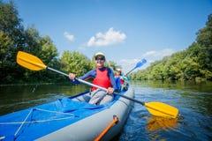 Vacaciones de verano - muchacha feliz con su madre kayaking en el río Fotografía de archivo