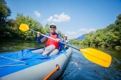 Vacaciones de verano - muchacha feliz con su madre kayaking en el río Foto de archivo libre de regalías