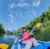 Vacaciones de verano - muchacha feliz con su madre kayaking en el río Fotos de archivo libres de regalías