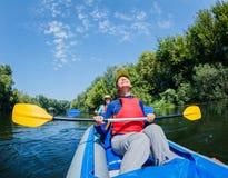 Vacaciones de verano - muchacha feliz con su madre kayaking en el río Imagen de archivo libre de regalías
