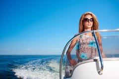 Vacaciones de verano - muchacha que conduce un barco de motor Foto de archivo