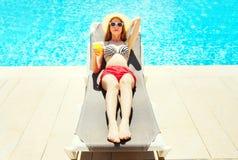 Vacaciones de verano - mujer bonita que descansa con el jugo de la taza en un deckchair fotos de archivo