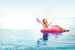 Vacaciones de verano Mujer en bikini en el colchón inflable del buñuelo en la piscina del BALNEARIO imagen de archivo