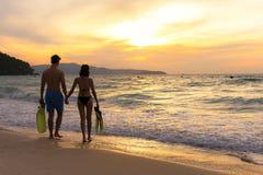 Vacaciones de verano Pares que caminan llevando a cabo las manos en tropical en el tiempo de la puesta del sol de la playa en día Imagen de archivo libre de regalías