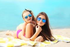 Vacaciones de verano, relajación, viaje - madre y reclinación de mentira del niño sobre la playa imagenes de archivo