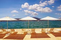 Vacaciones de verano Sombrillas y salones de la calesa en la playa montenegro Imagenes de archivo