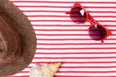 Vacaciones de verano, turismo, viaje, concepto del día de fiesta Cáscaras del mar, sombrero de la playa y manta rayada en blanco  Fotografía de archivo libre de regalías
